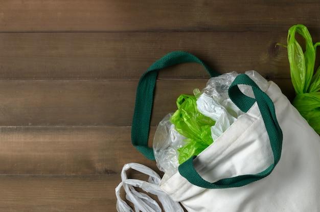 Sacos de plástico no saco de pano branco sobre fundo de madeira