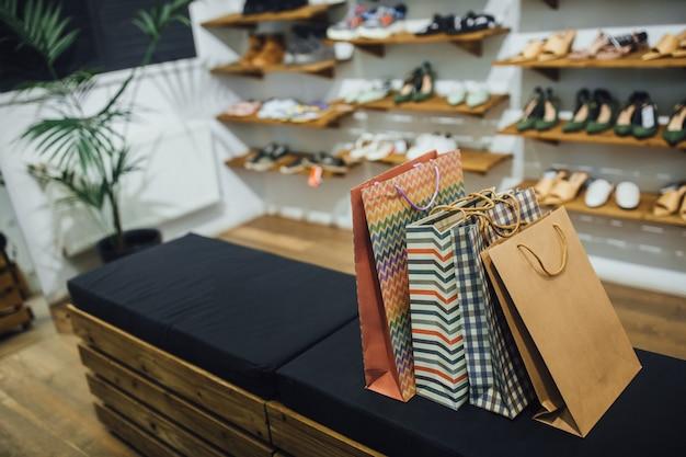 Sacos de presente nas prateleiras no fundo das prateleiras com sapatos na loja