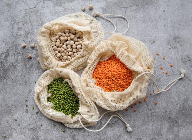Sacos ecológicos com diferentes tipos de leguminosas em uma superfície marrom