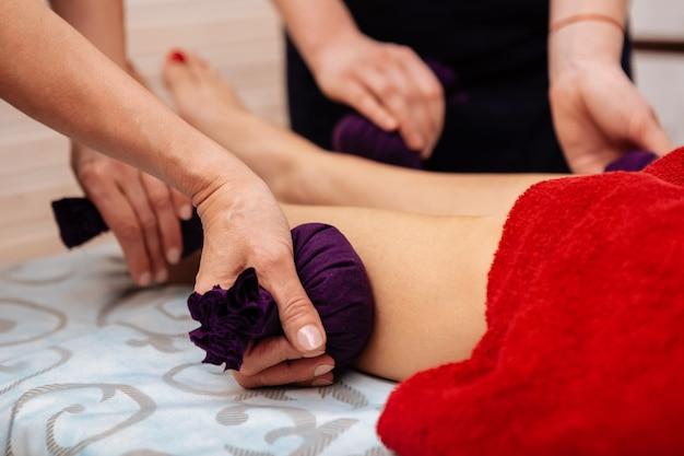 Sacos especiais de ervas. profissionais em salão de spa com técnica de massagem incomum e envolvendo bolsas de ervas