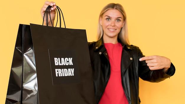 Sacos grandes de compras black friday segurados por uma mulher