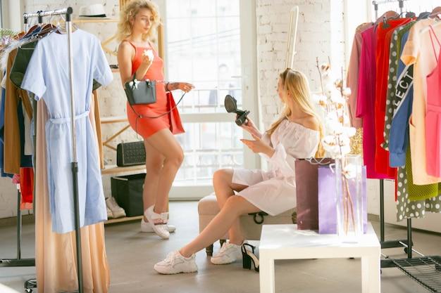Sacos minúsculos. desgaste, loja de roupas durante as vendas, coleção de verão ou outono. mulher jovem à procura de um novo traje. conceito de moda, estilo, ofertas, emoções, vendas, compras. novo shopping.