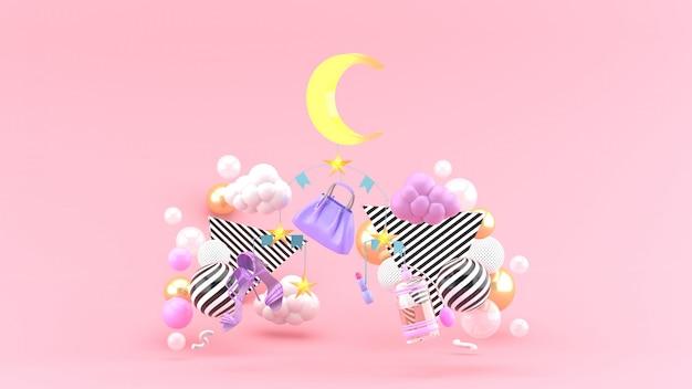 Sacos móveis, sapatos, lua e estrelas em meio a bolas coloridas em um espaço rosa