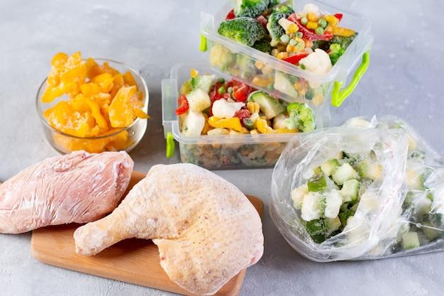 Sacos plásticos e recipientes com diferentes vegetais congelados e carnes na mesa, vista superior
