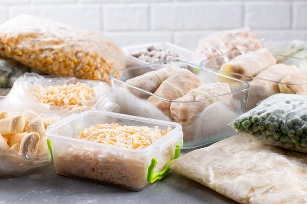 Sacos plásticos e recipientes com diversos produtos congelados, vegetais e carne na mesa