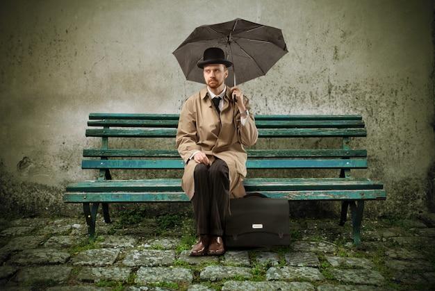 Sad elegante homem sentado com um guarda-chuva