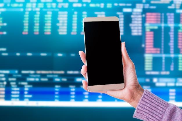 Saff segurando móvel com caneta e gráfico candlestick gráfico comércio forex dados de crescimento sinal digital do mercado de ações os indicadores de linha de tendência desfocam o fundo. plano de negócios de finanças de lucro de moeda de investimento.