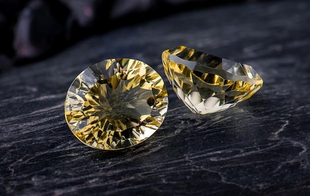 Safira de gema oval amarela com fundo escuro de rocha.