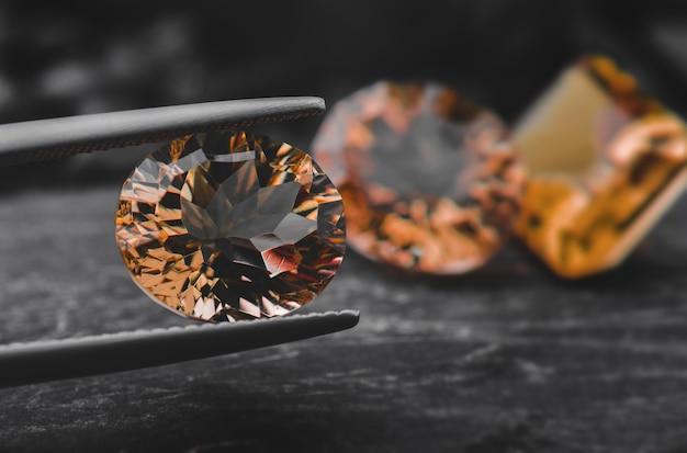 Safira de pedra preciosa de cor laranja com rocha escura
