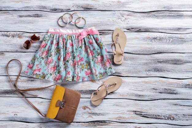Saia azul com bolsa marrom bicolor estampado floral e acessórios femininos de sandálias na vitrine da loja qu ...
