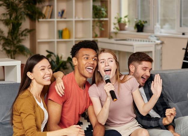 Saia com amigos alegres, jovens amigos multiculturais jogando karaokê em casa e cantando com