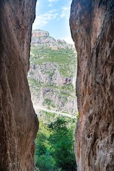 Saia da caverna para uma paisagem ensolarada com floresta e céu azul