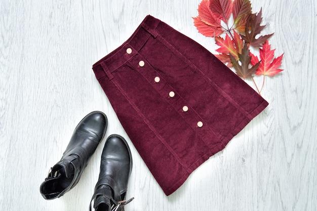 Saia de camurça cor de vinho, botas pretas e folhas vermelhas