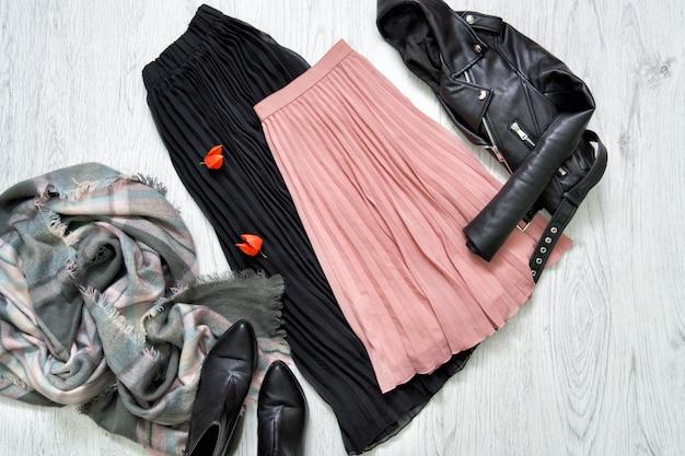 Saia, jaqueta, cachecol e botas pretas e rosa