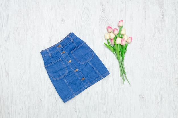 Saia jeans azul e tulipas cor de rosa.