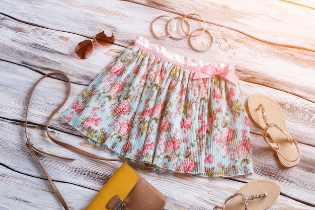 Saia leve floral e sandálias, óculos escuros, pulseiras e bolsa com seleção de acessórios para meninas ...