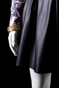 Saia preta e pulseira de ouro. mão de manequim com pulseira de ouro. novo acessório exclusivo para mulheres. elegante e caro.