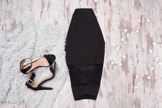 Saia preta e sapatos em madeira