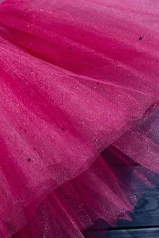 Saia tutu rosa para menina sobre fundo azul de madeira.