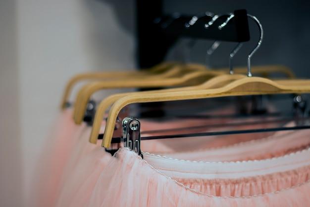 Saias cor-de-rosa penduradas em cabides na loja