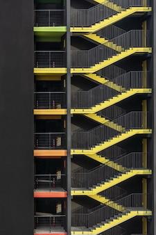 Saída de incêndio externa amarela brilhante do novo edifício de estacionamento multinível na cidade
