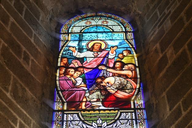 Saint junien, france - 30 de dezembro de 2020: vitrais na igreja com jesus cristo e pessoas pedindo cura
