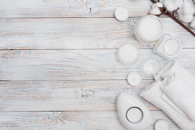Sais de banho e flores de algodão em fundo de madeira