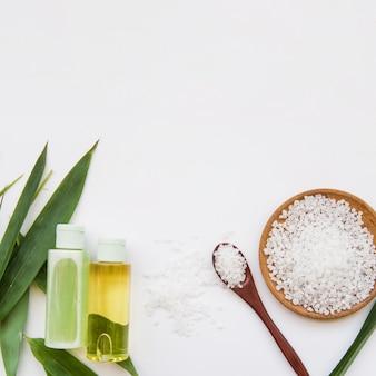 Sais de rocha; folhas e frascos de spray no fundo branco