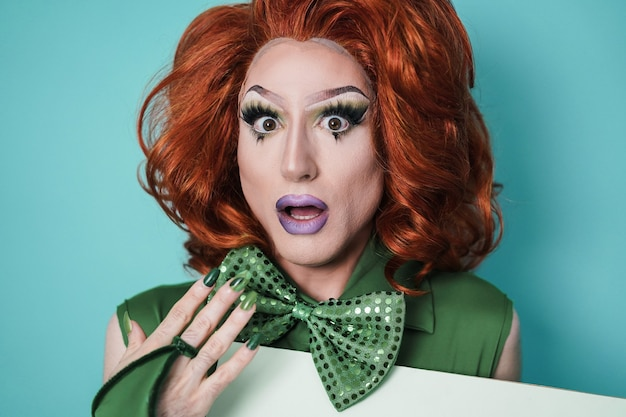 Saiu da drag queen olhando para a câmera com fundo turquesa - conceito lgbtq - foco no rosto