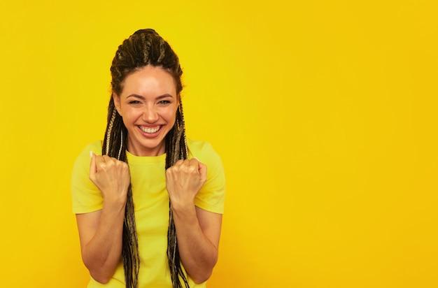 Saiu da mulher feliz posando na parede amarela.