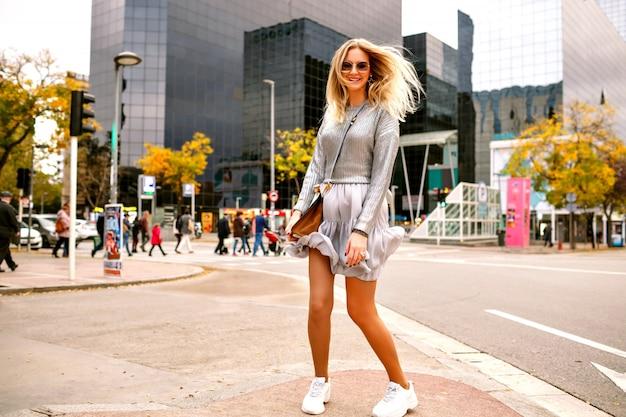 Saiu feliz mulher loira pulando dançando e se divertindo na rua perto de um edifício moderno, tênis elegante roupa de prata elegante, bolsa de luxo e óculos de sol, turista feliz em nova york.