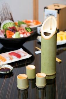 Sake em garrafa de bambu com comida japonesa