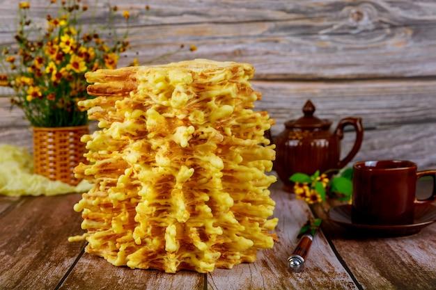 Sakotis de bolo em camadas tradicional lituano com chá na superfície de madeira.