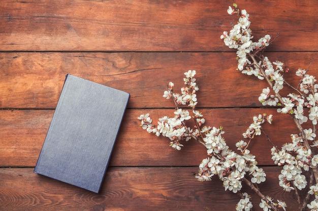 Sakura ramos com flores e um livro em uma superfície de madeira escura