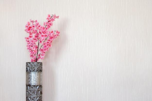 Sakura rosa em um vaso dentro de casa contra uma parede branca