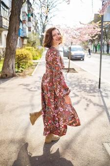 Sakura se ramifica com flores em uma árvore nas ruas da cidade. garota de mulher feliz girando na rua com sakura florescendo. sakura floresce.