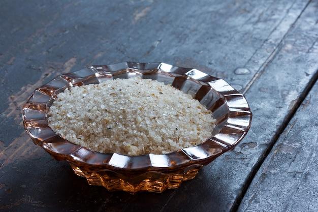 Sal adygei em um saleiro de vidro em uma velha mesa de madeira preta