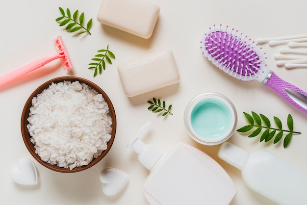 Sal branco na tigela com produtos cosméticos e escova de cabelo no fundo branco