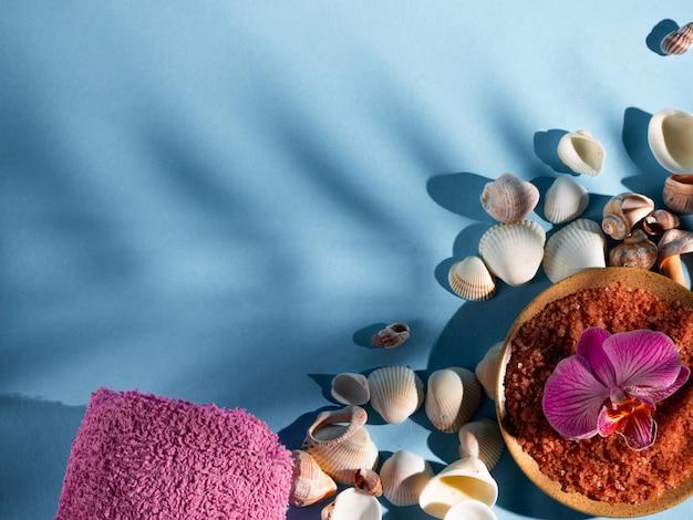 Sal de banho alaranjado em um pires com conchas, toalha e flor em um fundo azul com uma sombra de uma planta tropical. copyspace, flatlay. spa, relaxado, verão