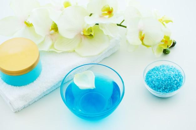 Sal de banho azul, creme corporal e conchas para spa