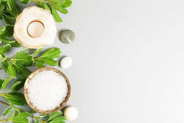 Sal de banho do mar branco em uma tigela de coco, vela e folhas verdes sobre um fundo cinza. conceito de spa e relaxamento.