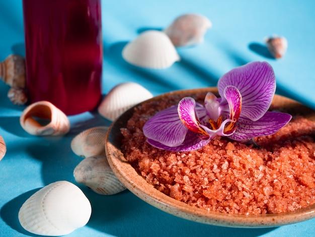 Sal de banho laranja em um pires com conchas, vela vermelha e flores sobre fundo azul com uma sombra de uma planta tropical. copyspace. spa, relaxado, verão