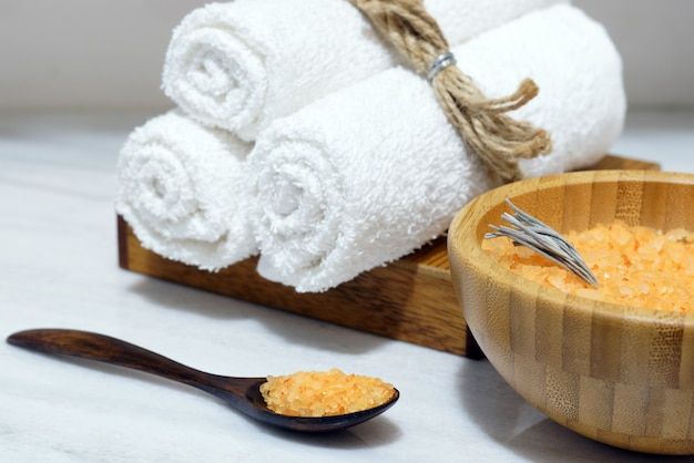Sal de banho laranja em uma tigela de madeira e colher e três toalhas brancas em uma caixa de madeira sobre uma mesa de mármore branco