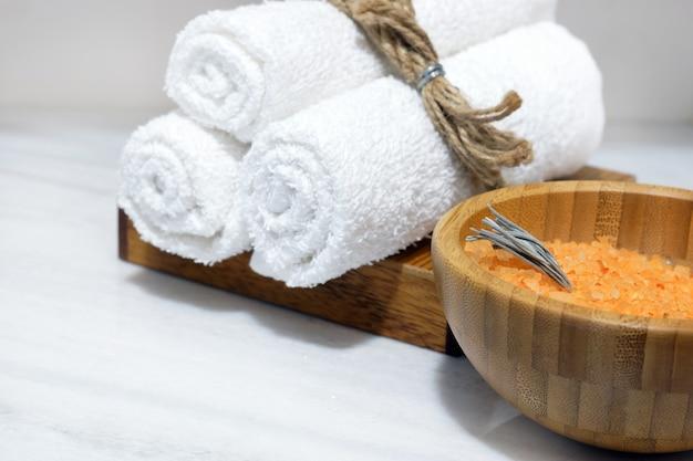 Sal de banho laranja em uma tigela de madeira e três toalhas brancas em um suporte de madeira sobre uma mesa de mármore branco
