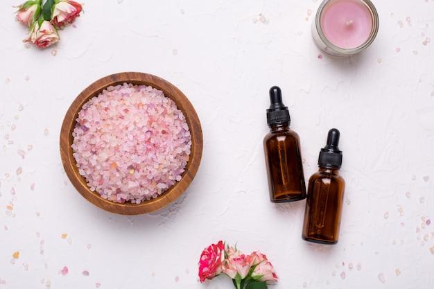 Sal de banho rosa e garrafas de óleo natural em branco