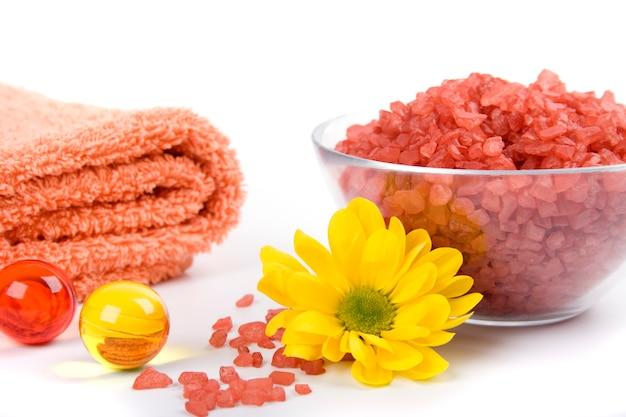 Sal de banho, toalhas e flor amarela