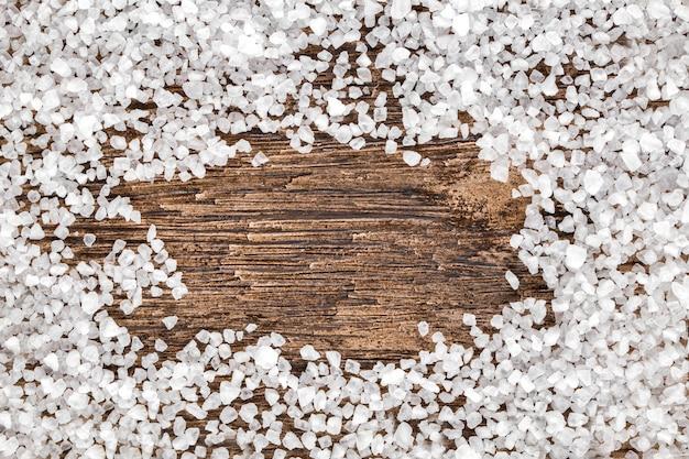 Sal de cristal do mar branco na mesa de madeira escura