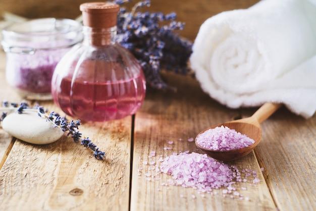 Sal de lavanda com produtos naturais de spa e decoração para banho em fundo de madeira