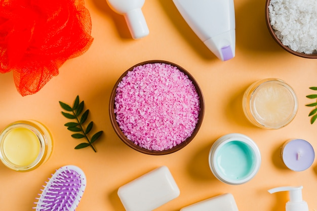 Sal do himalaia com produtos cosméticos em fundo colorido