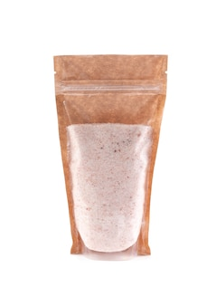 Sal do himalaia, moído em um saco de papel marrom. doy-pack com janela de plástico para produtos a granel. fechar-se. fundo branco. isolado.